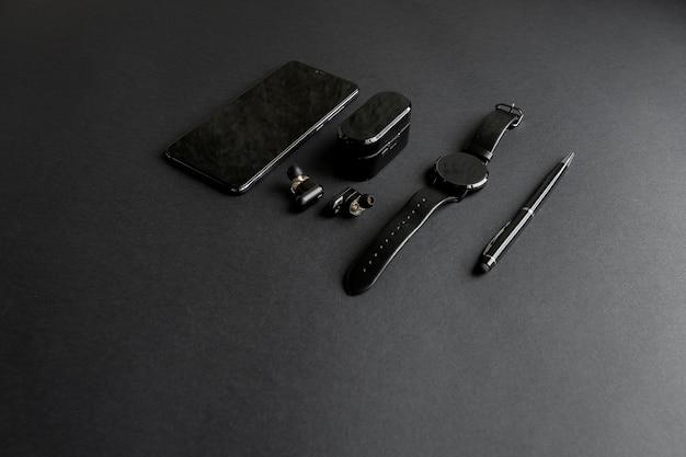 단색 배경에 남성의 아름다움을 위한 액세서리. 검은색 펜, 검은색 스마트 시계, 스마트폰 및 무선 헤드폰이 어두운 배경에 있습니다. 위에서 볼. 미니멀리스트 블랙 트렌드 2020.