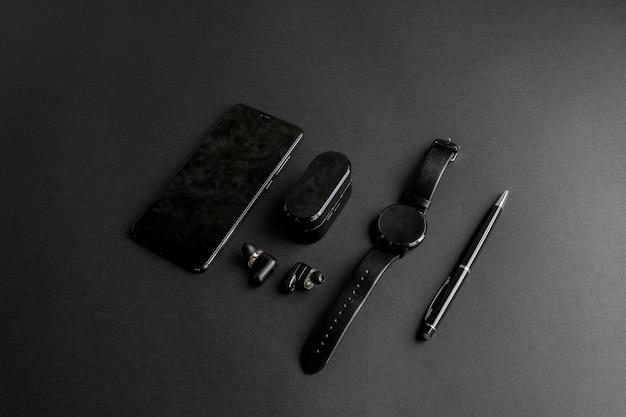 단색 배경에 남성의 아름다움을 위한 액세서리. 검은색 펜, 검은색 스마트 시계, 스마트폰, 그리고 어두운 배경의 무선 헤드폰. 위에서 볼 수 있습니다. 미니멀리스트 블랙 트렌드 2020.