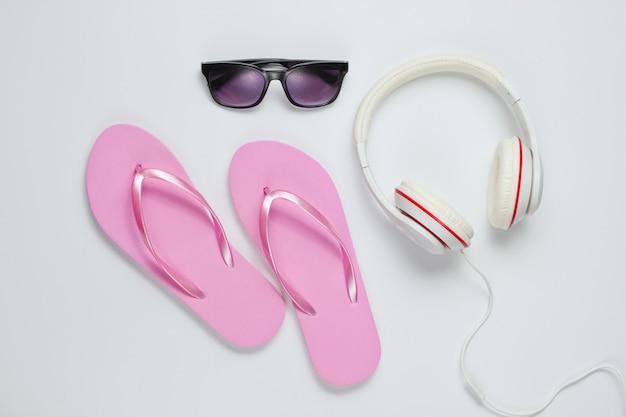 Аксессуары для отдыха на пляже. вьетнамки, наушники, солнцезащитные очки. студия снята на белом фоне. вид сверху