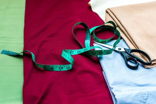 Фурнитура для шитья. концепция ремесла. разноцветные ткани, рулетка и ножницы крупным планом.