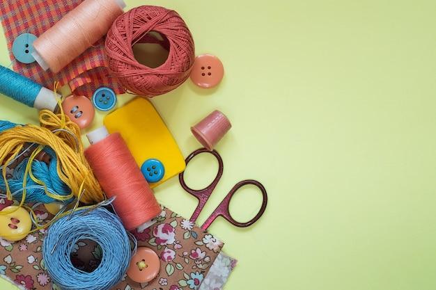 黄色の背景にパステルカラーの縫製用アクセサリー