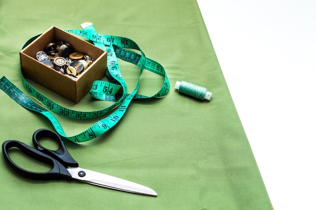Аксессуары для шитья. шитье бизнес-концепции. разноцветные ткани, рулетка, ножницы и кнопки крупным планом.