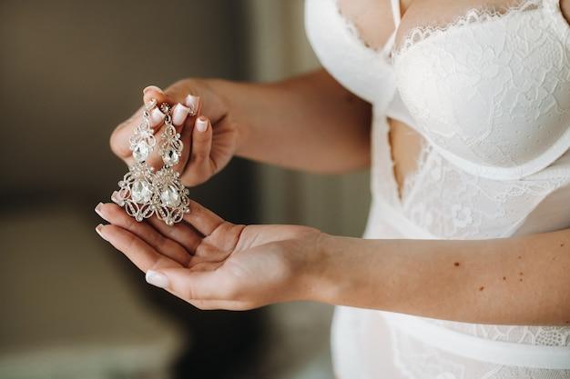 花嫁のためのアクセサリー。ベールのイヤリング。白い結婚式のイヤリング。テキストと広告のためのスペース。