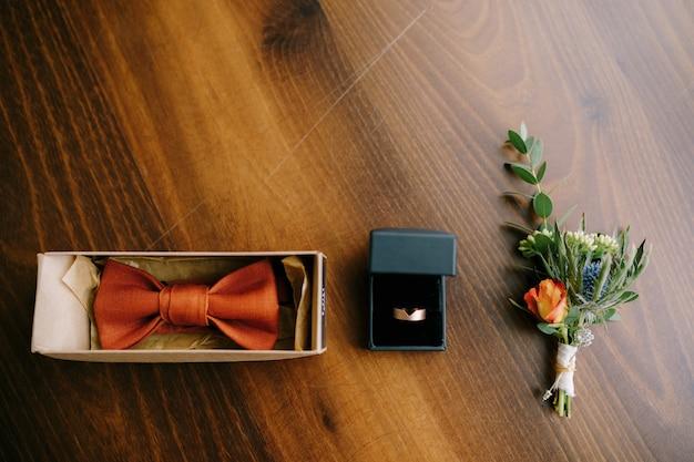 Аксессуары для жениха, галстук-бабочка, золотое обручальное кольцо и бутоньерка на деревянном полу подряд