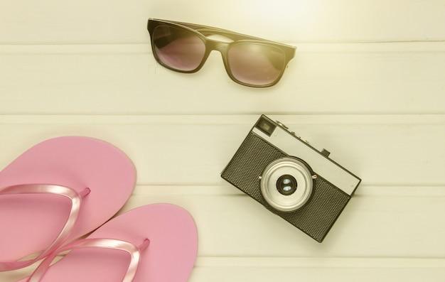 ビーチでの観光用アクセサリー。ビーチでの休暇。ビーチサンダル、レトロなカメラ、白い木の床にサングラス。上面図