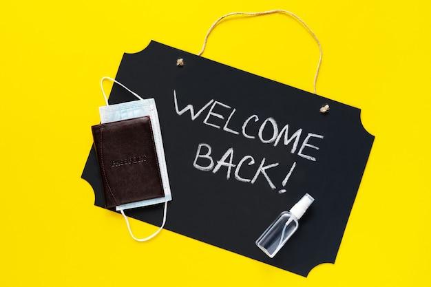 Аксессуары для путешественников и текст «добро пожаловать обратно» на желтом фоне. концепция путешествия коронавируса. пандемия.