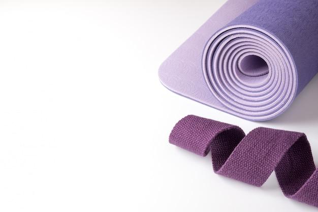 ヨガ、ピラティス、フィットネス用のアクセサリー。紫のヨガマットと白のベルト