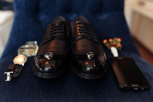 Accessories of a groom: shoes, boutonniere, phone, parfum and clock