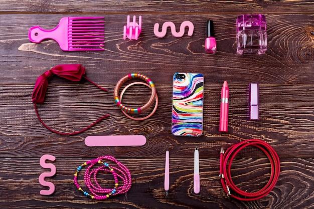 액세서리, 메이크업 및 전화. 나무에 스마트폰과 화장품입니다. 스타일리시한 룩을 완성해보세요. 단정한 외모의 디테일.