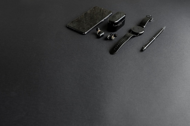 Accessories for men's beauty on a monochromatic background. black pen, black smart watch, smartphone and wireless headphones on dark background. view from above. minimalist black trend 2020.