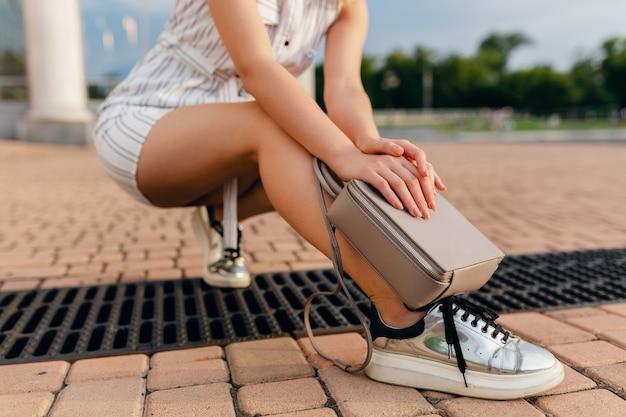 Аксессуары стильной женщины, идущей по городской улице в платье стиля летней моды, кроссовках, серой сумочке кошелька