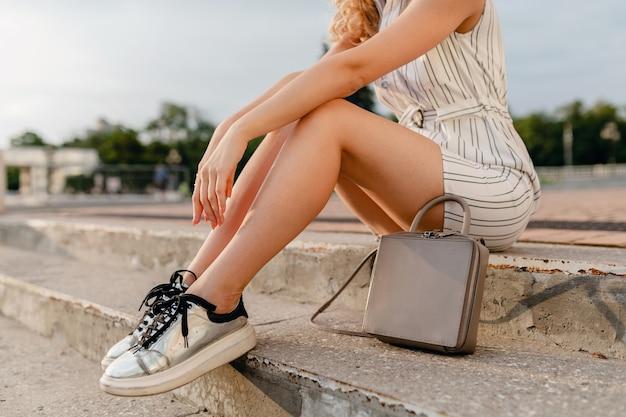 夏のファッションスタイルで街を歩くスタイリッシュな女性のアクセサリー、スニーカーの脚、灰色の財布のハンドバッグ