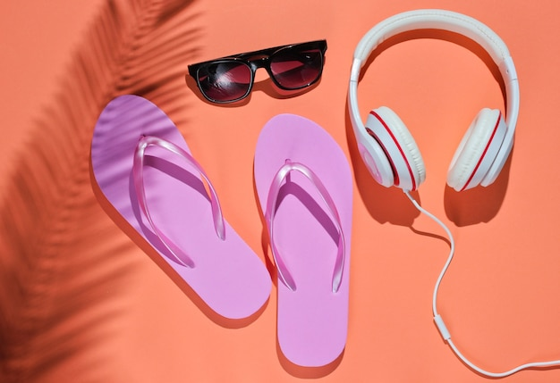Accessories for relaxing on the beach. flip flops, headphones, sunglasses. studio shot on pink background with palm leaf shadow. top view