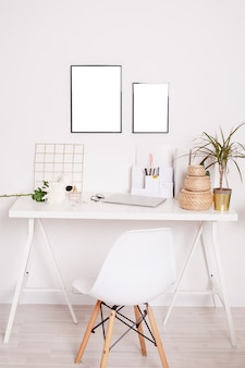 Accessories on shelf next to white chair at desk with laptop computer, plant and flowers in bright workspace vertical