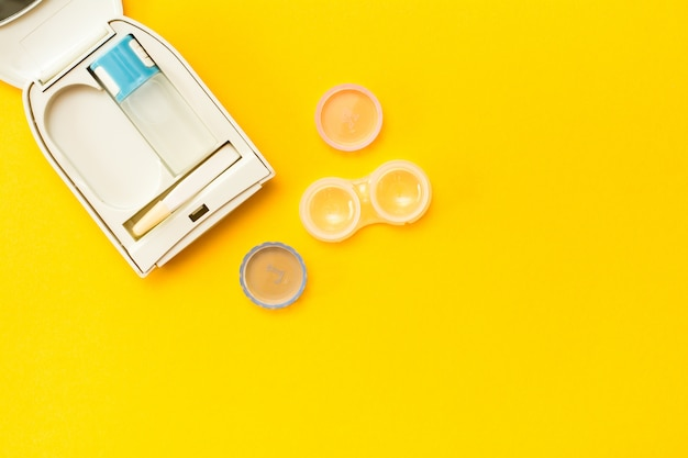 Accessories for storing lenses: a bottle of liquid, a container and tweezers in a case
