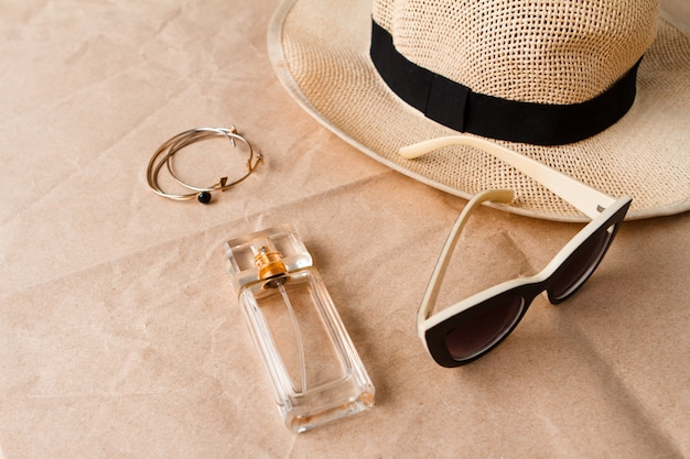 クラフトサーフェス上のアクセサリーサングラスの香水と帽子