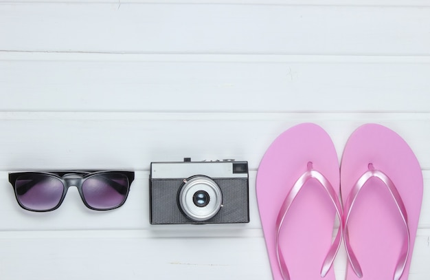 Accessories for tourism on the beach. beach vacation. flip flops, retro camera, sunglasses on white wooden floor.