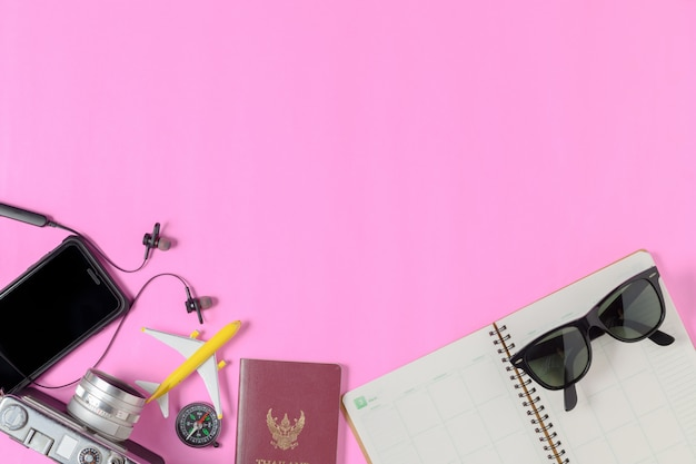 Accessories for travel on pink background, summer travel