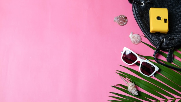 Accessories traveler camera black shoulder bag and sunglasses palm leaf. top view concept summer background.