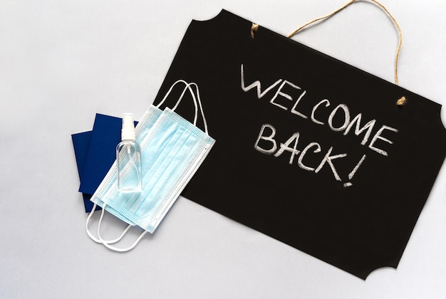 Accessories for travelers and text welcome back on a grey background. coronavirus travel concept. pandemic.