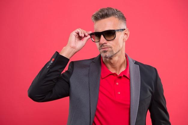 スーツをアクセサリー化します。オーダーメイドのスーツは、すべての着用者を引き立てます。自信の紳士。男ハンサム自信を持って成熟したファッションモデルはファッショナブルなスーツを着ています。ビジネススーツスタイル。高級衣料品店。