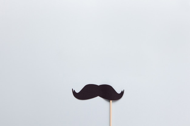 Accessory in form of black moustache on stick on grey background