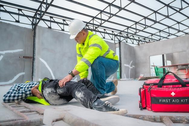 건설 현장에서 사고입니다. 건설 노동자의 직장에서 신체적 부상. 응급 처치 건설 현장에서 사고를 당한 건설 노동자를 도우십시오. 건설 작업 중 사고 시 응급 처치 도움.