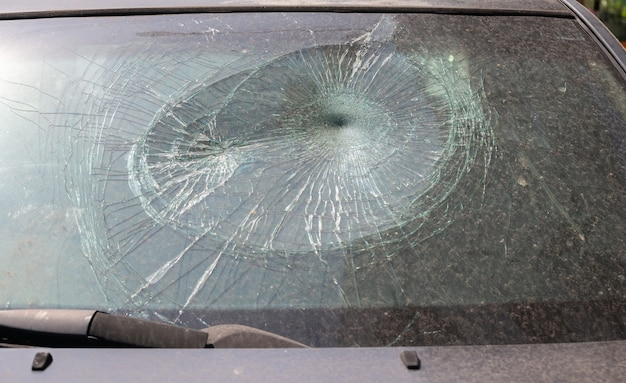 Accident crashed car with broken windshield and spiderweb cracking of laminated safety glass