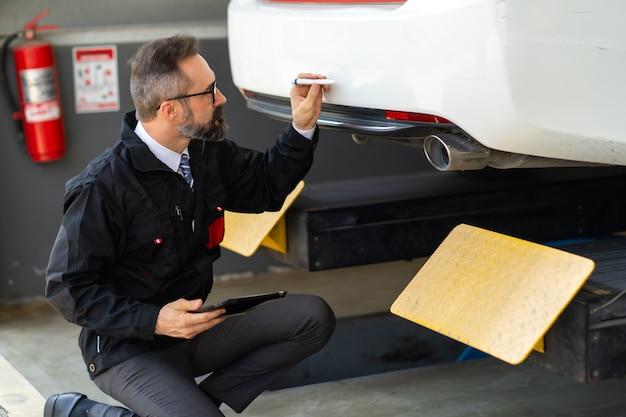 사고 조사관 도로에서 자동차 충돌로 인한 손상 차를 검사합니다. 차고에서 디지털 태블릿으로 흰색 차를 검사하는 자동차 보험 대리인.