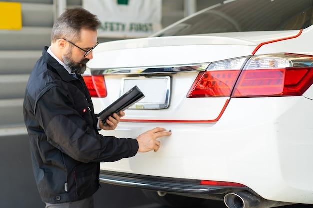 Инспектор дтп осмотрите автомобиль, поврежденный в результате автомобильной аварии на дороге