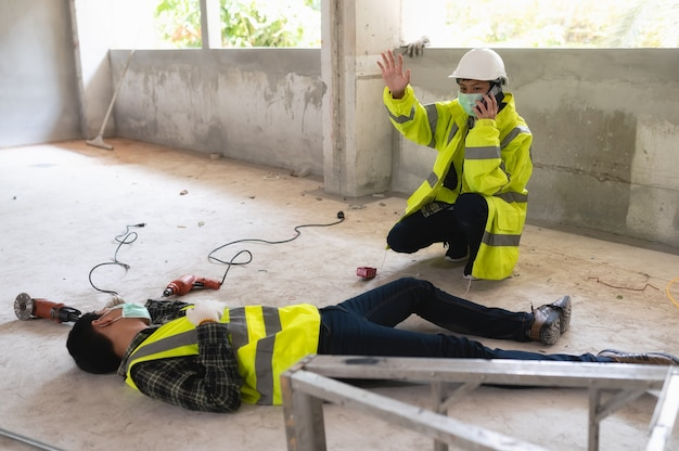 An accident of a man worker at the construction site and call to the safety officer for rescue and life-saving. selection focus on an injured person.