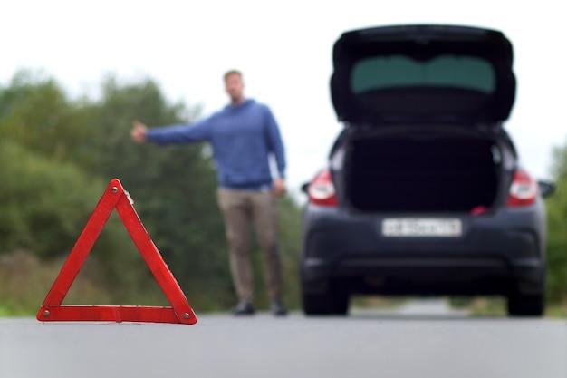 道路での事故。緊急三角表示板とぼやけた男がヒッチハイク