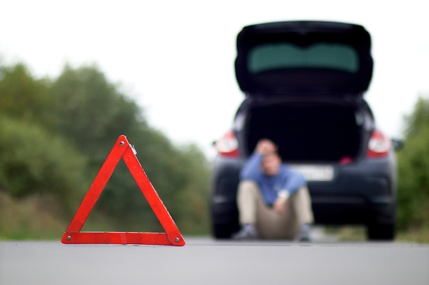 Авария на дороге. треугольник аварийной остановки и мужчина сидит возле поврежденной машины