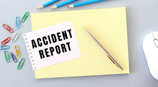 Accident report는 사무용품 옆에있는 노트북 위에 놓인 종이에 적혀 있습니다. 비즈니스 개념.