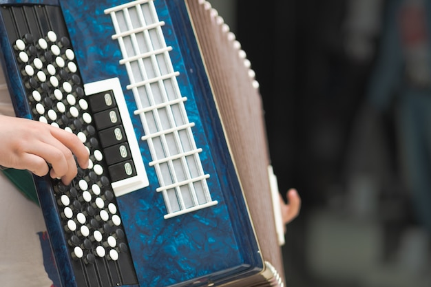 ミュージシャンの手のアコーディオン、クローズアップビュー。ストリートミュージックのイメージ、メロデオンを演奏する大道芸人