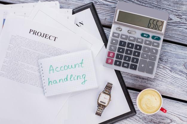 계정 처리 개념입니다. 흰색 나무 테이블에 계산기와 시계 시계가 있는 비즈니스 서류. 평면도 평면도.