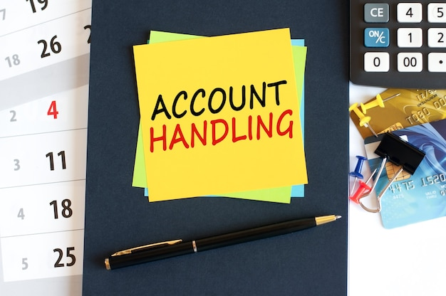 Account handling, text on yellow paper square shape on a blue background. notepad, calculator, credit cards, pen, stationery on the desktop. business, financial and education concept. selective focus.