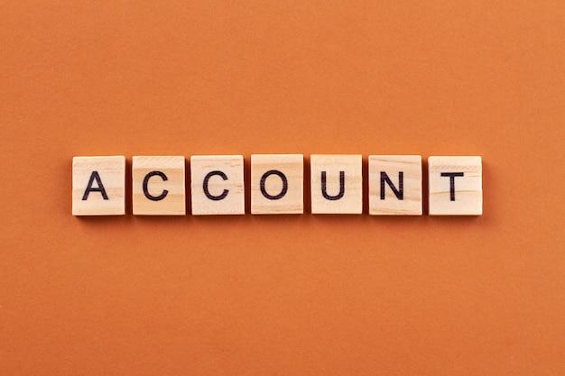 アカウントは財務活動の記録です。オレンジ色の背景に分離された文字でアルファベットブロック。