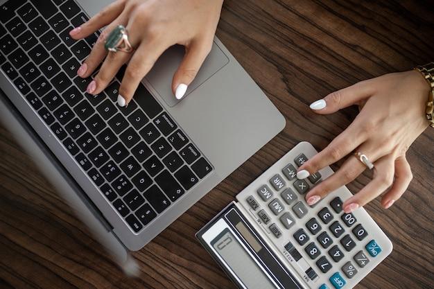 Бухгалтер на работе, женские руки с калькулятором и ноутбуком.