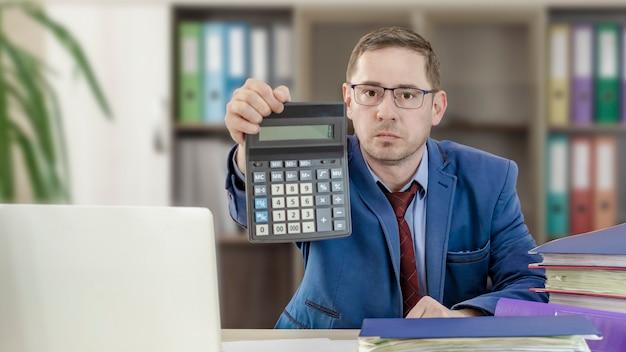 オフィスの彼の机にいる会計士のビジネスマンは、電卓を差し出します財務チェック