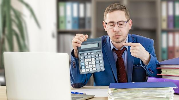 オフィスの彼の机の会計士のビジネスマンは、電卓に指を示しています