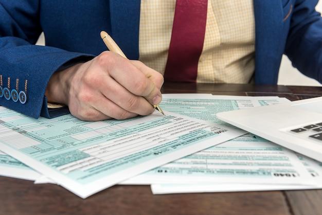 Бухгалтер заполняет налоговую форму. финансовый документ бухгалтерского учета бизнесмена. оформление документов, время для налогов