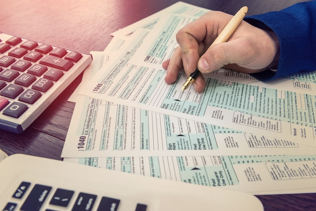Accountant fills in tax form. businessman accounting finance document. paperwork, time for tax