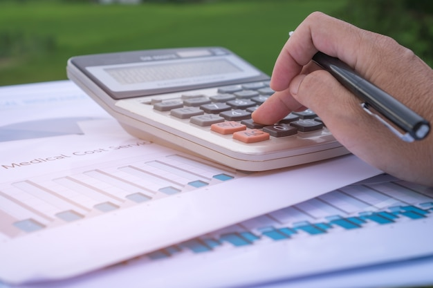 Accountant hands calculate financial report graph, counting on calculator