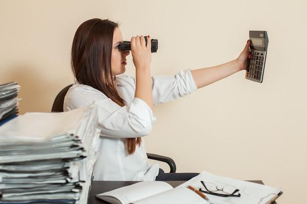 Accountant looks through binoculars on calculator