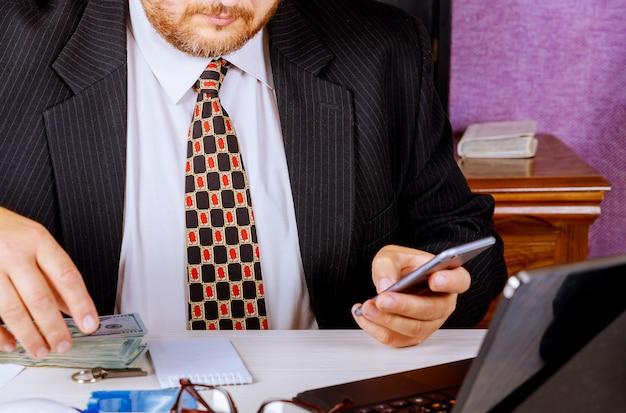 ドル紙幣を数える机に座っているスーツを着ている会計士の男、スマートフォンを呼び出してメモを作る銀行員