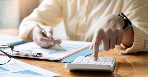 会計士や簿記係が電卓、会計ファイナンスの概念を使用して机に取り組んでいます。