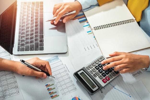 会計士は、事務室で会議チームのためにラップトップを指しています。コンセプトファイナンスと会計