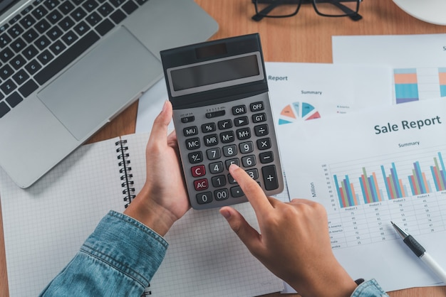 The accountant's hand is using the calculator. for cost analysis profit and loss and tax calculation concept preparation of financial statements