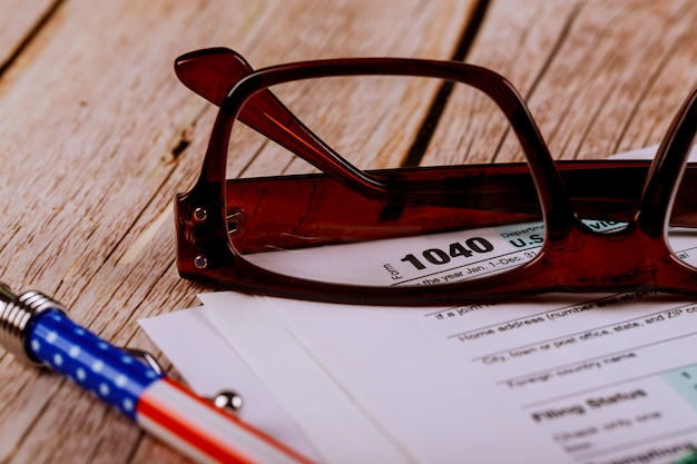 Accountant's office documents tax form focus on 1040, shallow depth of field with pen, glasses